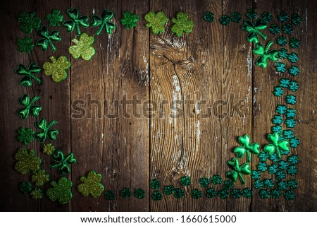 St Patricks Day frame of glittery shamrocks over an old rustic wood background. St.Patrick's day holiday symbol. Lucky charms. Top view, copy space.