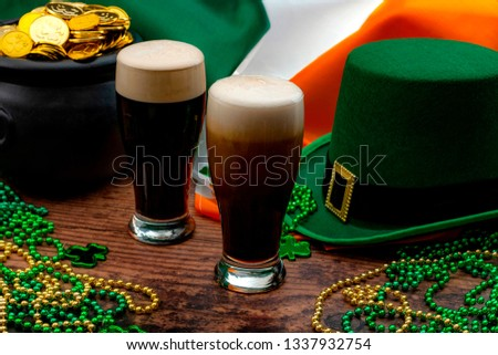 St Patricks day party and Irish celebration of patron saint concept theme with frothy glasses of dry stout, green hat with a buckle, a pot of gold, the flag of Ireland and beads with shamrock in a pub Stock photo ©