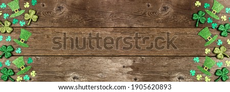 St Patricks Day shamrock and leprechaun hat double border. Top view over a rustic wood banner background with copy space.