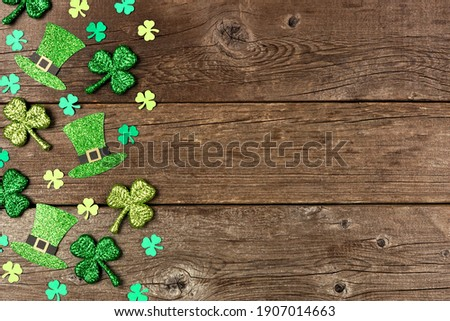 St Patricks Day shamrock and leprechaun hat side border. Above view over a rustic wood background with copy space.