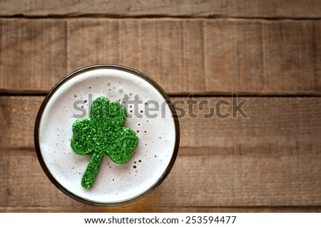 St. Patricks Day Shamrock Floating in Frothy Beer Mug on rustic wood board background with room or space for copy, text, your words.  Closeup Above View Horizontal with warm tone