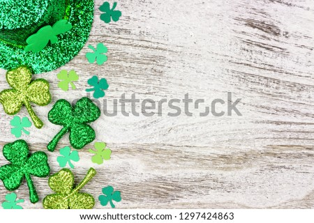 St Patricks Day side border of shamrocks with leprechaun hat over a rustic white wood background