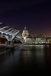 St. Paul's Cathedral from the river banks with millennium bridge across the river. The photo is taken with a dslr camera in long exposure setting