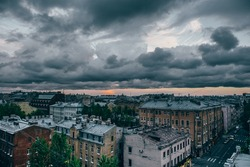 St. Petersburg cityscape in moody tones, dark dramatic clouds, old buildings, panoramic view from roof
