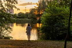 St. Petersburg. Russia. July 16, 2021. An unrecognizable woman stands on the bank of a pond in the park.