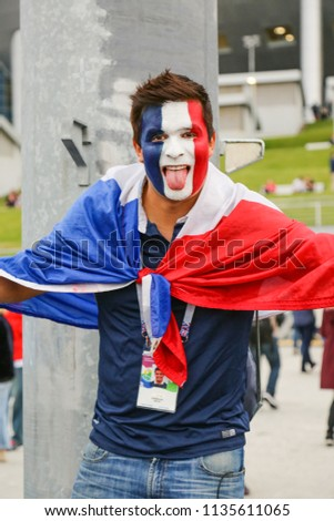 St. Petersburg, Russia - July 10, 2018: Emotional fan of France national football team at semi-final FIFA World Cup championship. Man supporter with painted french flag on face showing tongue. #1135611065