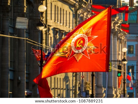 ST. PETERSBURG, RUSSIA - MAY 9, 2018: Soviet and Russian flags on the parade on Nevsky Prospect on Victory Day (commemoration of the surrender of Nazi Germany in 1945). #1087889231