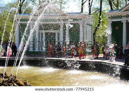 ST. PETERSBURG, RUSSIA - MAY 21: Wind band in fountain spatters on Annual ceremonial fountains opening in Peterhof palace-park ensemble on May 21, 2011 in St. Petersburg, Russia