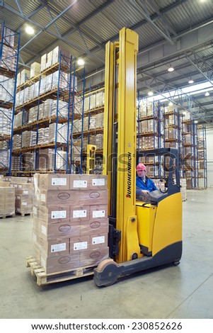 St. Petersburg, Russia - November 21, 2008: The driver of a yellow forklift truck operates, in warehouses, sitting in the workplace. A fork lift truck moves stacked pallets. Forklift palletiser.