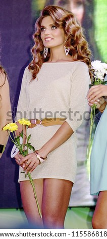 ST. PETERSBURG, RUSSIA - OCTOBER 13: Beautiful brunette girl with flowers during final stage of the contest Russian Beauty on October 13, 2012, in St.Petersburg, Russia