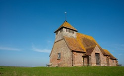 St. Thomas Becket church on a bright sunny afternoon, is an English 13th century religious building which sits isolated on marshland at Fairfield, Kent, part of Romney Marsh.