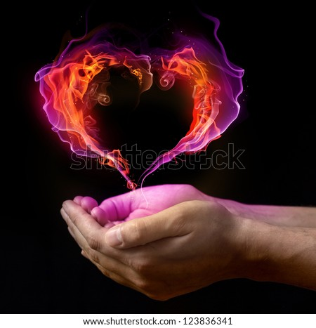 St. Valentin's burning heart on the hands against dark background
