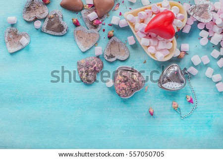 St Valentine's heart shaped decorations, chocolates and sweets on pheasant blue background. Top View #557050705