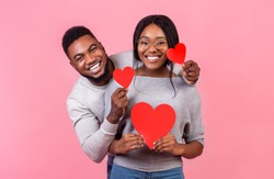 St. Valentines day concept. Cheerful afro couple in love holding red valentines cards and embracing, pink studio background