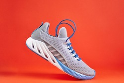 Stability and cushion running shoes. New unbranded running sneaker or trainer on orange background. Men's sport footwear.