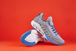 Stability and cushion running shoes. New unbranded running sneaker or trainer on orange background. Men's sport footwear. Pair of sport shoes.
