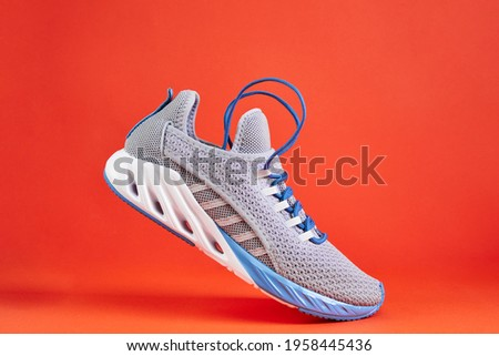 Stability and cushion running shoes. New unbranded running sneaker or trainer on orange background. Men's sport footwear. Stock fotó ©
