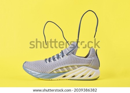 Stability and cushion running shoes. New unbranded running sneaker or trainer on yellow background. Men's sport footwear. Pair of sport shoes. Stock fotó ©