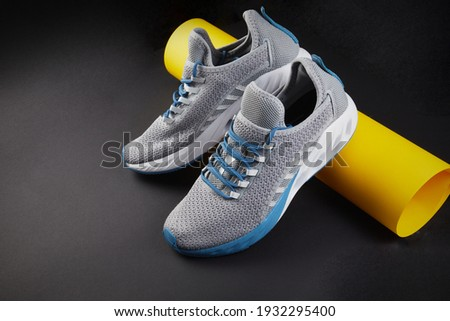Stability and cushion running shoes. New unbranded running sneaker or trainer with yellow paper tube. Men's sport footwear. Pair of sport shoes. Stock fotó ©