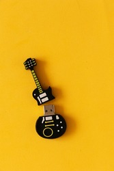 Stable usb disk in the form of a guitar on a yellow table. Files saved on usb disk