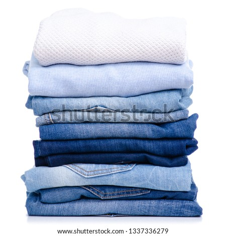 Stack blue jeans and white blue shirt, sweater, t-shirt clothes on white background isolation #1337336279