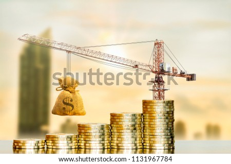 Stack coin with increase and tower crane and hoist brake with money bag on photo blur cityscape background, Loan and budget  for construction real estate concept.