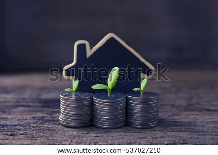 stack coins and house wood model ,concept idea for save and purchase house,growth business time.