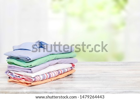 Stack colorful clothes. Pile of folded cotton shirts on a bright table with space for your display product montage against abstract blurred natural light green background. Summer fashion.