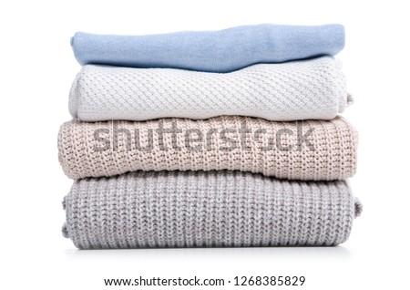 Stack folded sweaters on white background isolation #1268385829