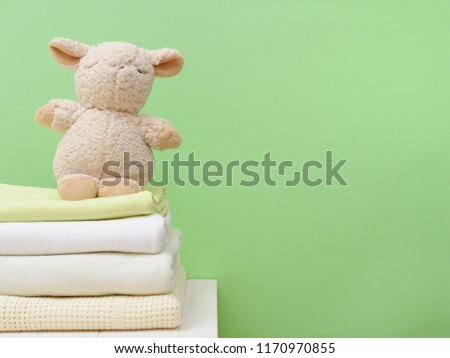 Stack light blankets and decorative toy lamb on a greeen background isolation.