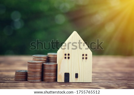Stack money coins on the wooden table with a simulated wooden house on the background tree green nature in the garden with a copy space upper side. Business and financial loans for homes concept. Photo stock ©