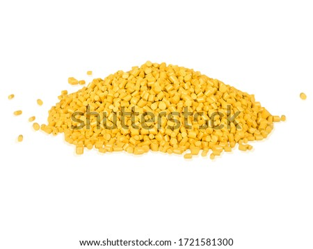 Stack of a yellow plastic polymer granules on a white background, Pile of yellow plastic granulate on white background