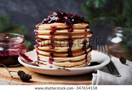 Stack of american pancakes or fritters with strawberry and blueberry jam in white plate on wooden rustic table decorated Christmas tree, delicious dessert for breakfast in winter, vintage style