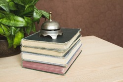 Stack of antique books with a vintage bell on top;  A neat pile of books with a very old bell resting on top.