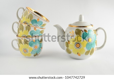 Stack of antique ceramic cups, teapot on a white background\n