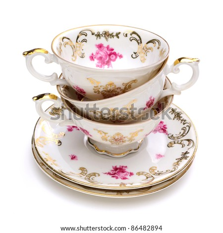 Stack of antique tea cups on white background