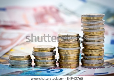 Stack of ascending Euro coins on banknote money background.