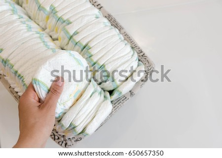 Stack of baby disposable diapers and Pacifier over white background #650657350