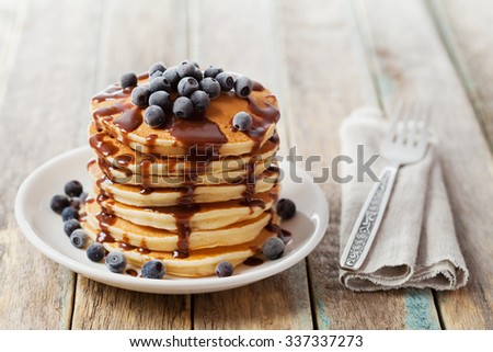 Stack of baked pancakes or fritters with chocolate sauce and frozen blueberries in a white plate on a wooden rustic table, delicious dessert for breakfast