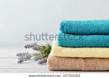 Stack of bath towels with lavender flowers on light wooden background closeup