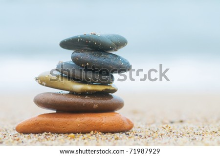 Stack of beach stones on sand. Ocean in the background