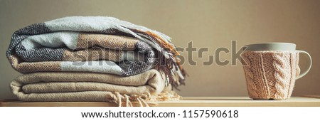stack of beige checkered wool blankets and cup on a wooden chest. autumn - winter concept of home warmth and comfort. toned, long banner #1157590618
