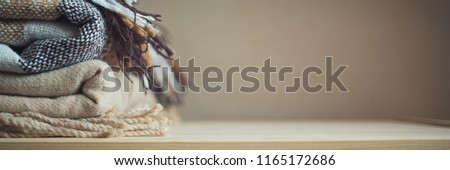 stack of beige checkered wool blankets on a wooden chest. autumn - winter concept of home warmth and comfort. toned, copy space, long banner