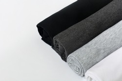 stack of black, grey and white (monochrome) t-shirt rolled up on white background, copy space