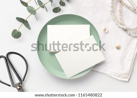 stack of blank business cards on a white feminine styled desk with mint bowl, decorative scissors, linen napkin and eucalyptus twigs. minimalist mock up, flat lay / top view #1165480822