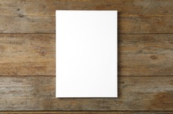 Stack of blank paper sheets for brochure on wooden background, top view. Mock up