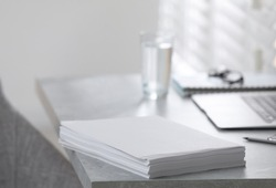 Stack of blank paper sheets on grey table in office, closeup