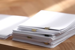 Stack of blank paper with binder clips on wooden table, closeup