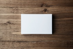Stack of blank white business cards on wooden background Horizontal