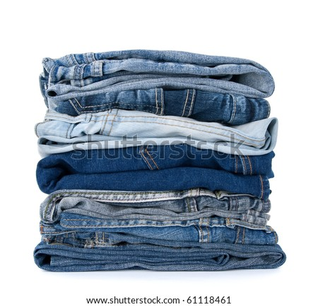 Stack of blue denim clothes on white background, jeans and jacket.